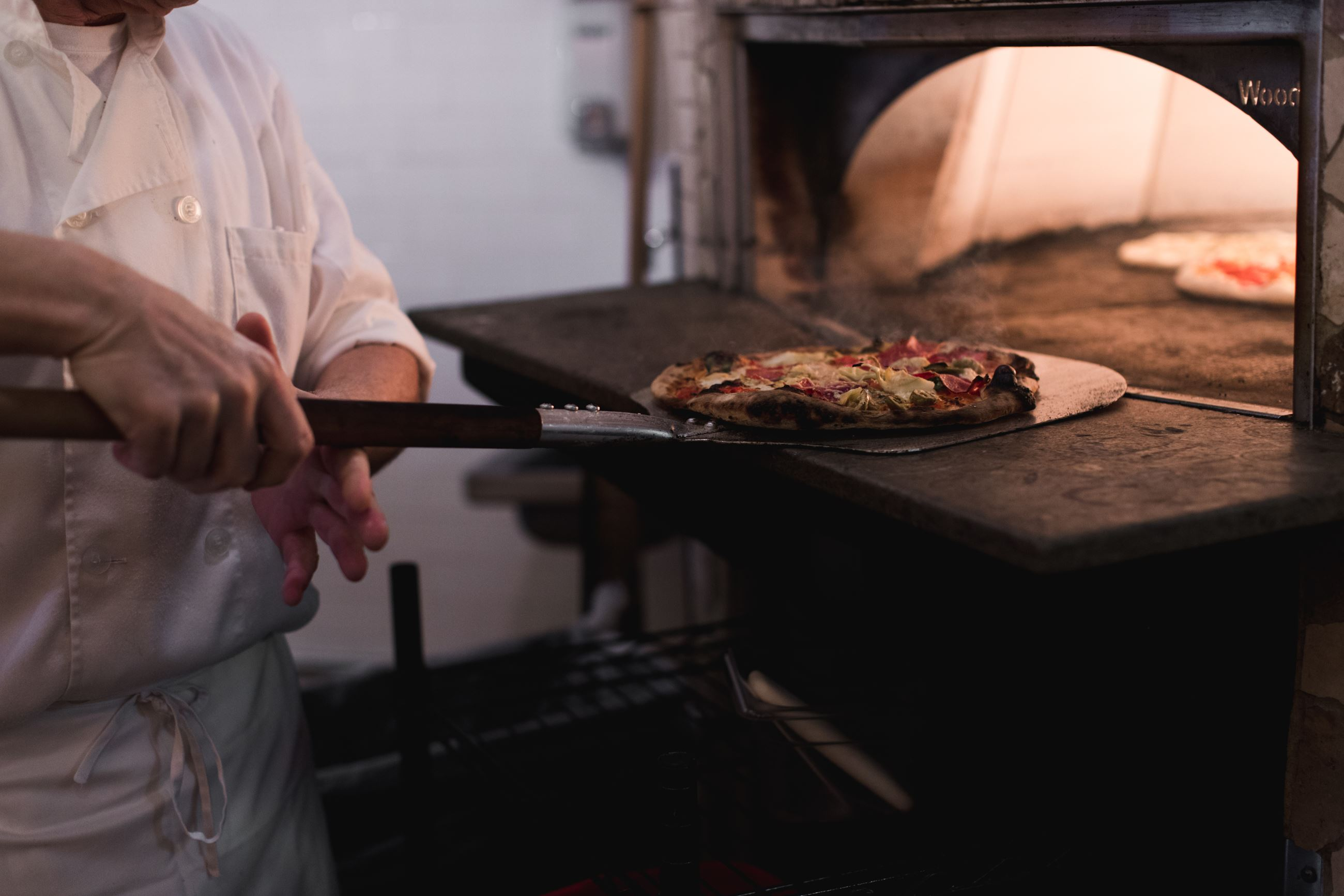 A photo of a pizza being put into a pizza oven